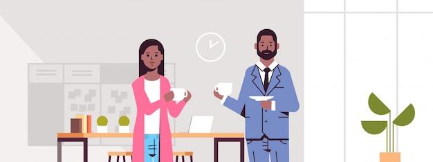 Paar trinkt cappuccino-geschäftsmannfrau, die während des treffens kaffeepausenkonzept modernes büroinnenporträt horizontal diskutiert