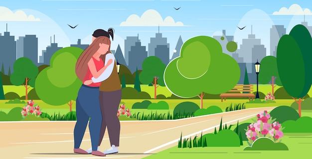 Paar umarmt übergewichtige mannfrau, die zusammen steht und spaß im romantischen datum der fettleibigkeit des stadtparks hat