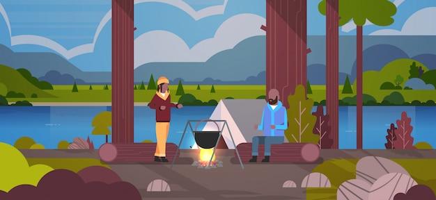 Paar wanderer mann frau kocht mahlzeiten in bowler kochenden topf am lagerfeuer in der nähe von lager zelt camping konzept landschaft natur fluss berge hintergrund horizontal in voller länge