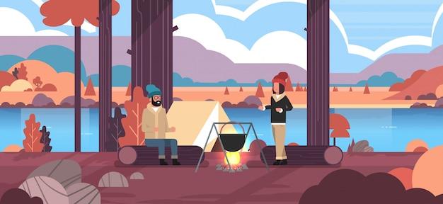 Paar wanderer sitzen auf log mann frau kochen mahlzeiten in bowler kochtopf am lagerfeuer in der nähe von camp zelt camping konzept herbst landschaft natur fluss berge