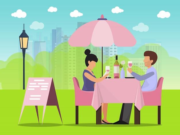 Paardatum im café draußen. mann und frau sitzen am tisch, trinken wein und reden