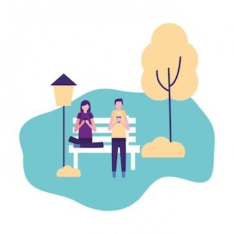 Paare, die handys im park verwenden