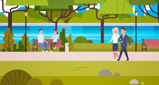 Paare von den geschäftsleuten, die draußen öffentlich den entspannenden städtischen park gehen