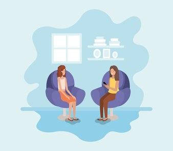 Paare von Frauen im Wohnzimmer unter Verwendung der Technologie