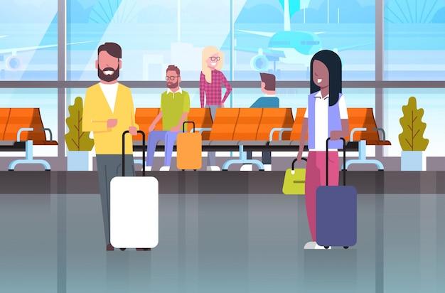 Paare von reisenden mit koffern an wartehalle