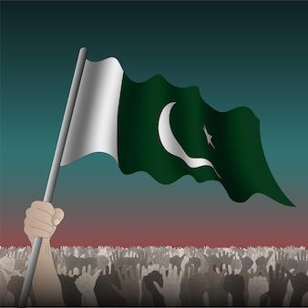 Pakistan schwenkt flagge in der hand unter menge.