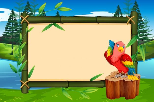 Papagei auf bambusrahmen mit copyspace