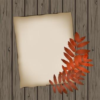 Papierblatt mit herbstlaub auf hölzerner hintergrundbeschaffenheit.