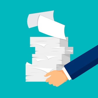 Papierkram und büroalltag. hand hält papierblätter stapeln. haufen weißer papiere