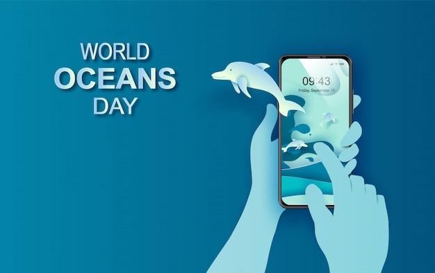 Papierkunst und schnittkonzept des weltmeertags. feier zum schutz des meeres und zur erhaltung des wasserökosystems. blaues origami-bastelpapier der meereswellen. delfine springen auf handy mit hand