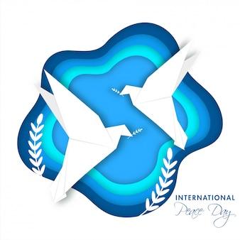Papierschicht geschnittener hintergrund mit fliegenden tauben und olivenblattzweigen für den internationalen friedenstag.
