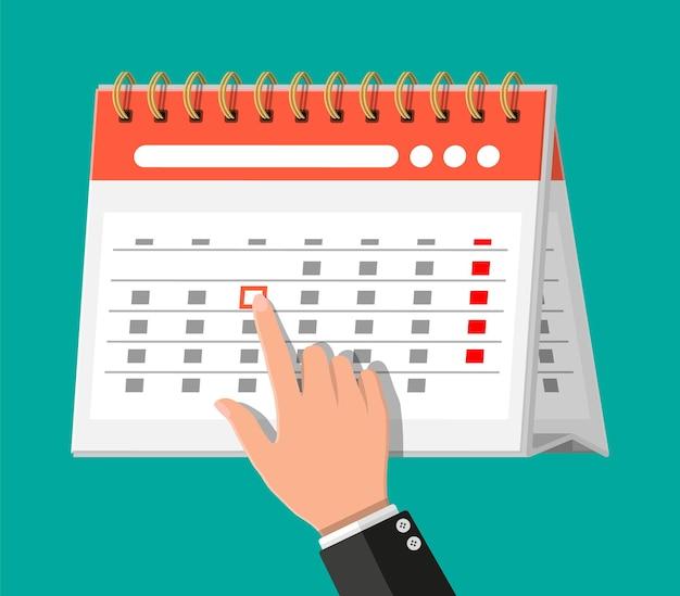 Papierspirale wandkalender und hand.