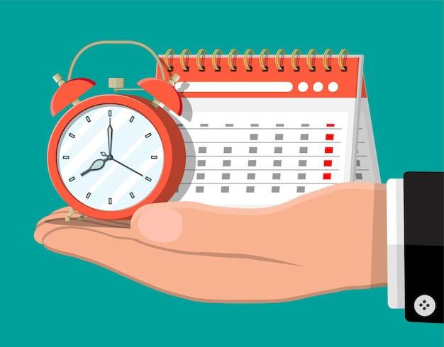 Papierspirale wandkalender und uhren in der hand. kalender und wecker. zeitplan, termin, veranstalter, arbeitszeittabelle, zeitmanagement, wichtiges datum.
