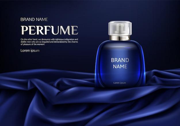 Parfümglasflasche auf blauer seide gefaltetem gewebe
