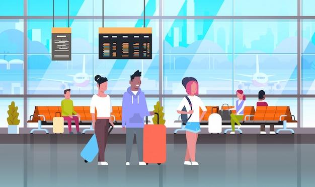 Passagiere im flughafen mit gepäck in wartehalle oder abflughalle