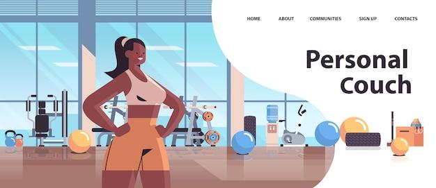 Persönlicher fitnesstrainer der afroamerikanerfrau, der im sportgymnastik-trainingstraining des gesunden lebensstilkonzeptporträts kopierraum steht