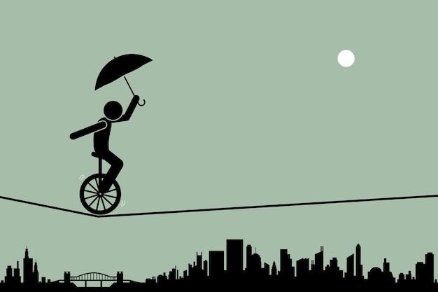 Person, die ein einrad reitet und es mit einem regenschirm balanciert, der durch ein drahtseilseil mit stadtbildschattenbild im hintergrund geht.