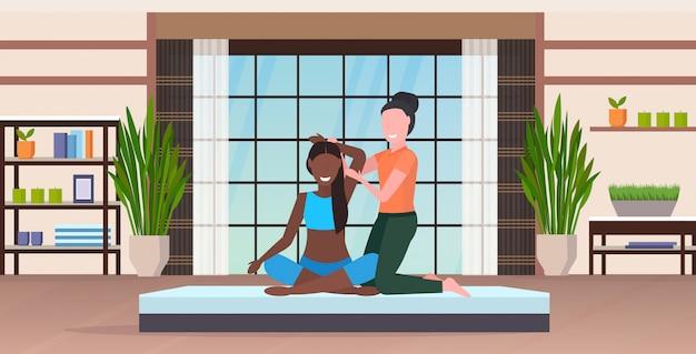 Personal trainer macht dehnübungen mit mädchen fitness instructor hilft frau, muskeln zu trainieren trainingskonzept modernes yoga studio interieur in voller länge horizontal