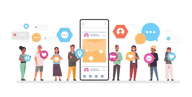 Personengruppe, die verschiedene arten von kommunikationssymbolen hält, mischen rasse männer frauen, die zusammen in der nähe von smrtphone bildschirm online mobile app soziales netzwerkkonzept stehen