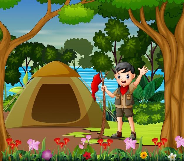 Pfadfinderjunge, der rote fahne auf campingplatz hält