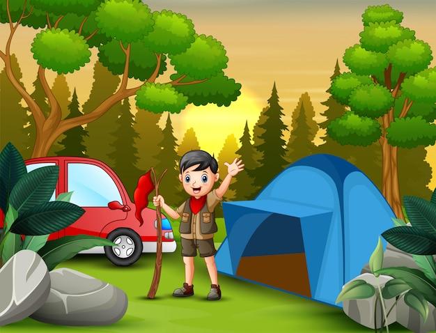 Pfadfinderjunge mit der roten fahne, die nahe einem zelt steht