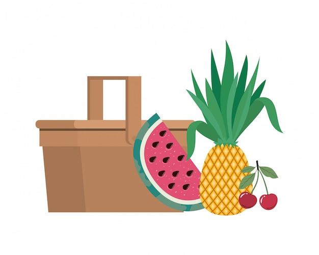 Picknickkorb mit tropischen früchten auf weiß