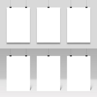 Plakatmodell, das an büroklammern hängt. realistische poster rahmen vorlagensatz ein. weiße pappkartons mit bindemitteln. schreibwarenzubehör, büroartikel. sammlung von leeren plakaten