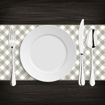 Platte mit löffel, khife und gabel auf einer hölzernen tabelle