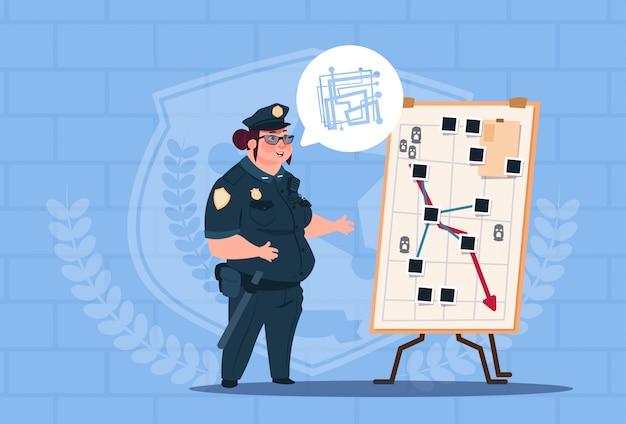 Polizeifrau-planungs-aktion auf dem weißen brett, das einheitlichen weiblichen schutz auf blauem ziegelstein-hintergrund trägt