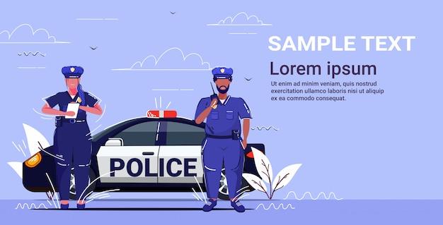 Polizist, der walkie-talkie-polizistin benutzt, die feine berichtsmischungsrassenpolizisten schreibt, die nahe patrouillenauto-straßenverkehrssicherheitsvorschriften-konzeptkopierraum stehen