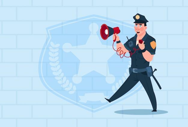 Polizist-griff-megaphon, das einheitlichen polizisten-schutz über ziegelstein-hintergrund trägt