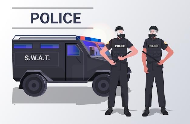 Polizisten in taktischer ausrüstung bereitschaftspolizisten paaren zusammen in der nähe von auto-demonstranten