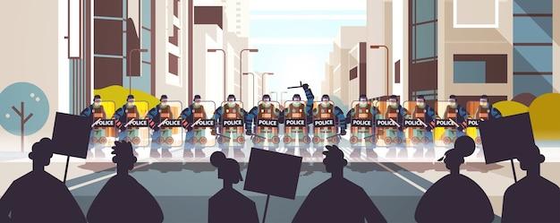 Polizisten in voller taktischer ausrüstung bereitschaftspolizisten, die straßenprotestierende mit plakaten während zusammenstößen kontrollieren demonstrationsprotestunruhen massenkonzept stadtbild horizontal