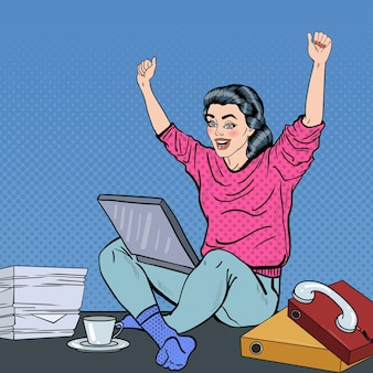 Pop art aufgeregte junge frau mit laptop, der auf dem schreibtisch mit papieren sitzt. illustration