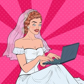 Pop art braut mit laptop. junge glückliche frau im hochzeitskleid, das online einkauft.