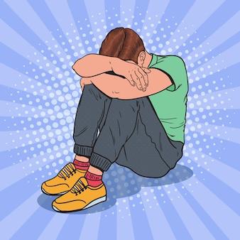 Pop art depressiver junger mann, der mit den händen auf dem kopf auf dem boden sitzt. depression und frustration.