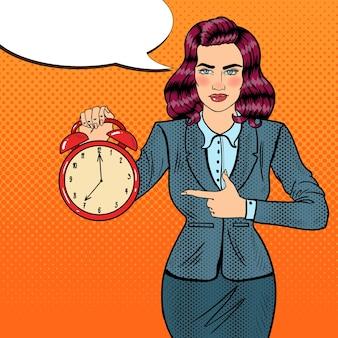 Pop-art-geschäftsfrau, die wecker hält. zeit zu arbeiten.