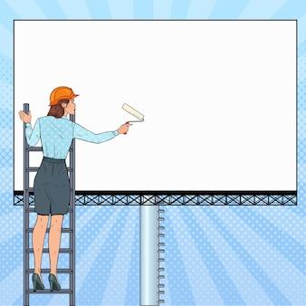 Pop-art-geschäftsfrau im helm mit leerer plakatwand. arbeitnehmerin, die banner anwendet. werbekonzept.