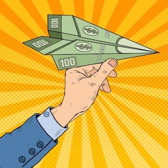Pop-art-geschäftsmann-hand, der dollar-papier-flugzeug wirft