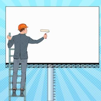 Pop-art-geschäftsmann im helm mit leerer plakatwand. männlicher arbeiter, der banner anwendet. werbekonzept.