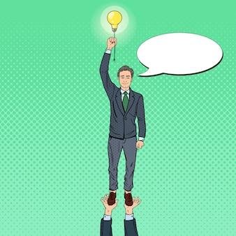 Pop art geschäftsmann mit glühbirne. teamarbeitskonzept.