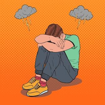 Pop art gestresster junger mann, der auf dem boden mit den händen auf dem kopf sitzt. depression und frustration.