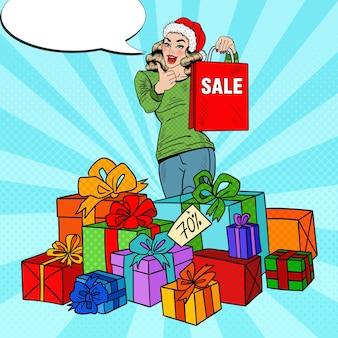Pop art glückliche frau in der weihnachtsmütze mit einkaufstasche und riesigen geschenkboxen auf weihnachtsverkauf.