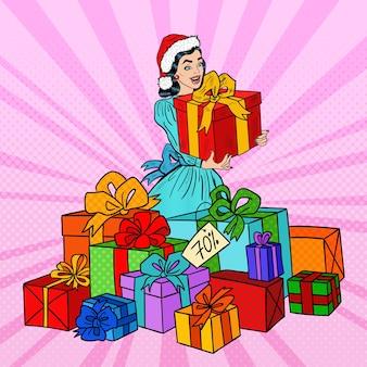 Pop art glückliche frau in der weihnachtsmütze mit großen geschenkboxen auf weihnachtsverkauf.
