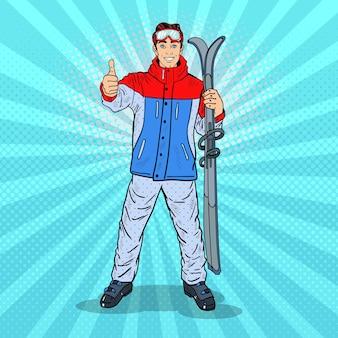 Pop-art-glücklicher junger mann auf ski-feiertagen, die daumen hoch gestikulieren. illustration