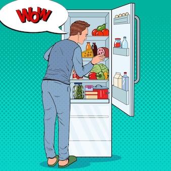 Pop art glücklicher mann, der in kühlschrank voller lebensmittel schaut