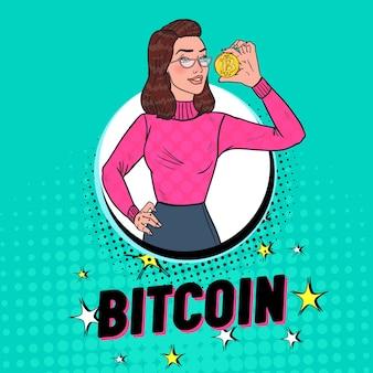 Pop art hübsche frau, die goldene bitcoin-münze hält. kryptowährungskonzept. werbeplakat für virtuelles geld.