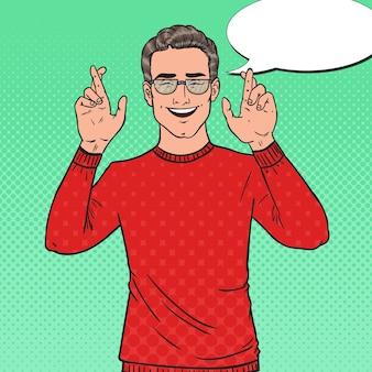 Pop art hübscher junger mann gekreuzte finger. kerl macht einen wunsch.