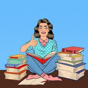 Pop art junge frau, die auf dem bibliothekstisch sitzt und buch mit handzeichen daumen hoch liest. illustration