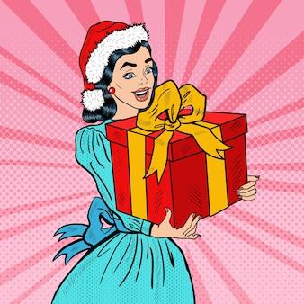 Pop art junge glückliche frau, die weihnachtsgeschenkbox hält. illustration